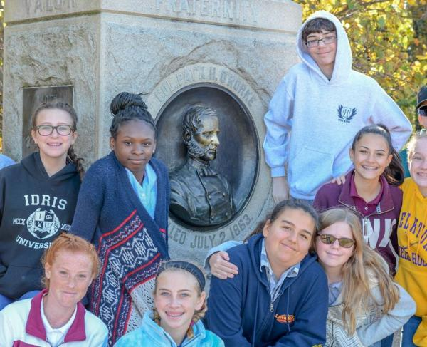 Students post with their teacher in front of a marker at Gettysburg.