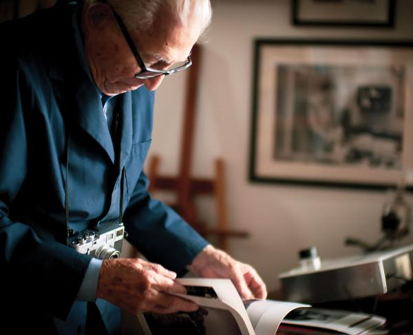 WWII Photographer Tony Vaccaro Looking Through Book