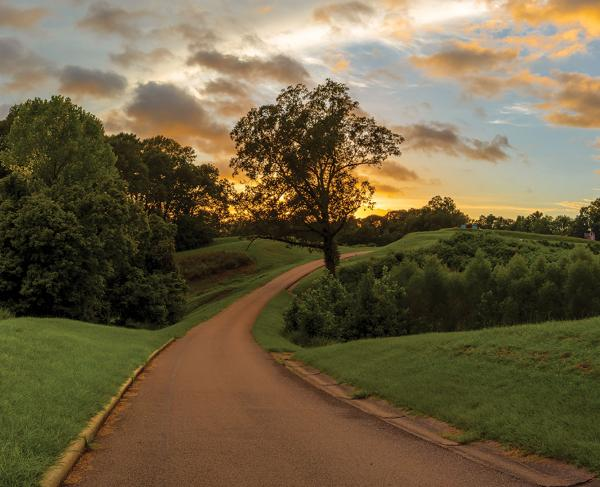 A paved path leads up a hill to a monument in the far distance, under a colorful sunset.